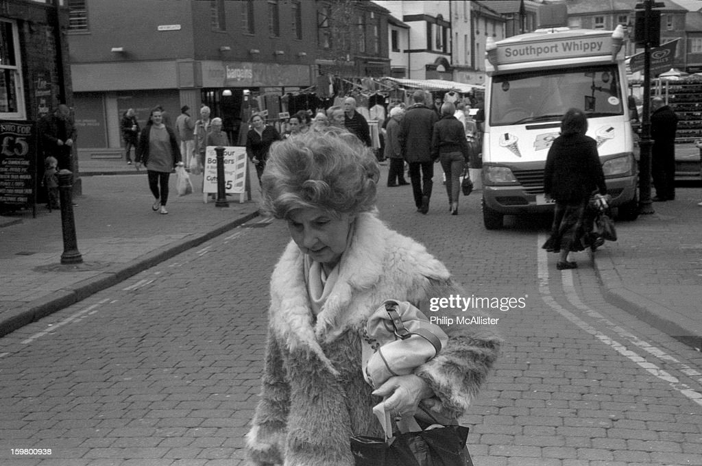 CONTENT] A glamorous but elderly lady walks through a busy market town.Her hair is a boufant style of the 1960s. She is clutching a handbag.