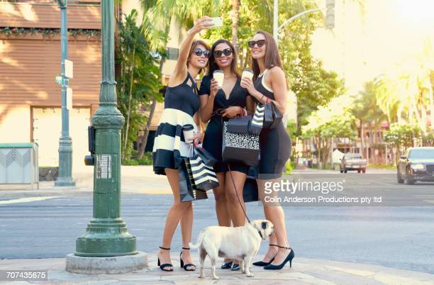 Glamorous friends posing for cell phone selfie in city