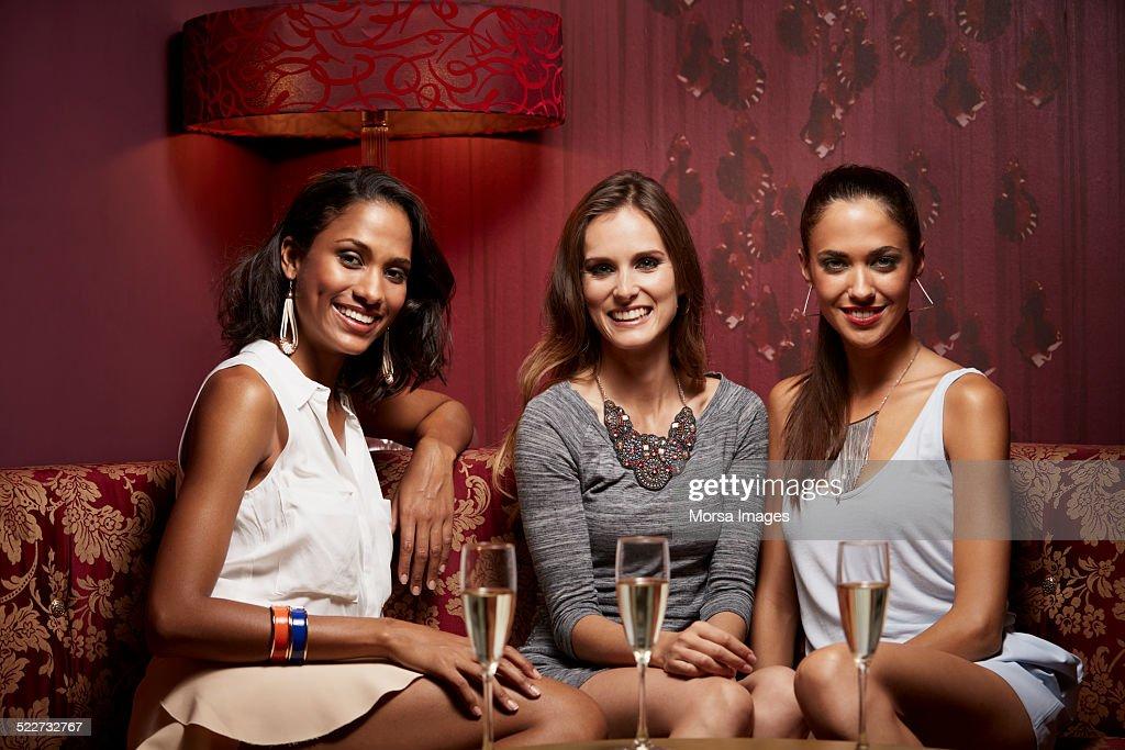 Glamorous friends sitting on sofa in nightclub