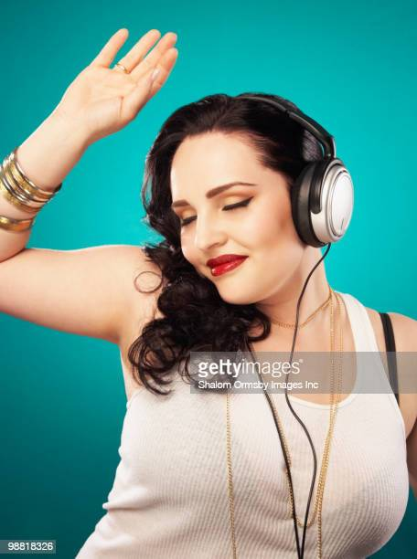 Glamorous Hispanic woman listening to headphones
