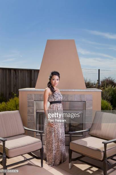 Glamorous mixed race woman near outdoor fireplace