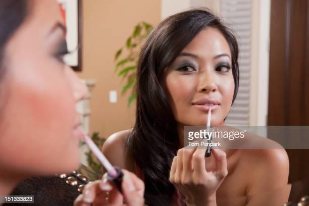 Glamorous mixed race woman putting on makeup