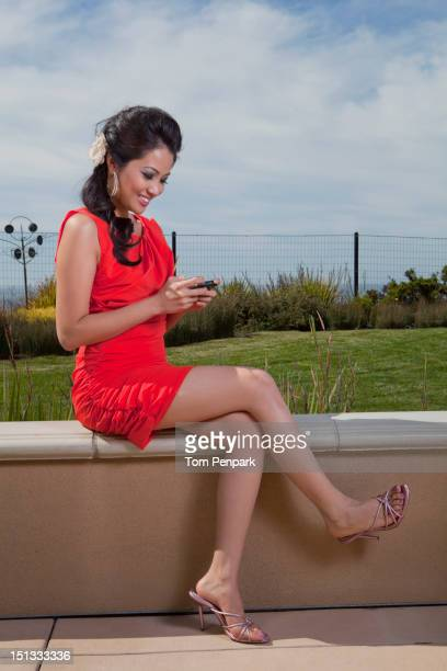 Glamorous mixed race woman text messaging on cell phone