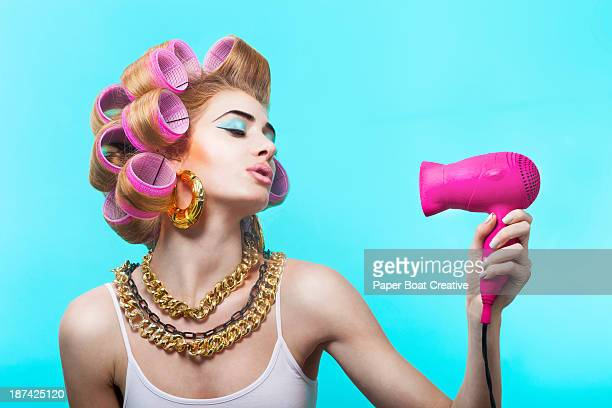 Glamorous woman blow drying her curled hair
