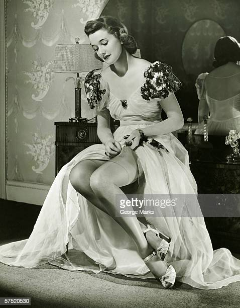 Glamorous woman in evening gown adjusting stockings, portrait, (B&W)
