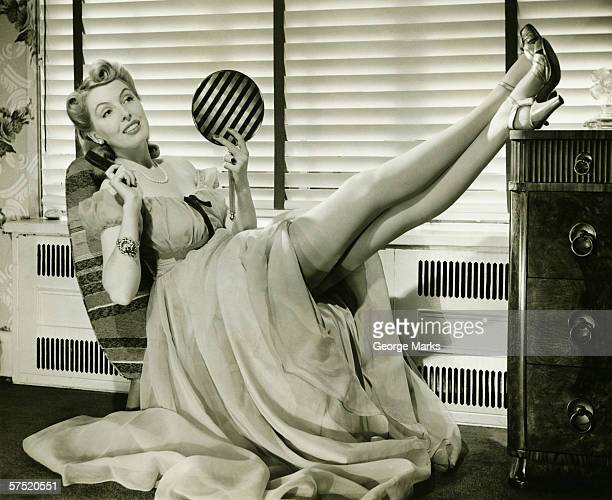 Glamorous woman in evening gown holding hand mirror, legs on cabinet, (B&W), portrait