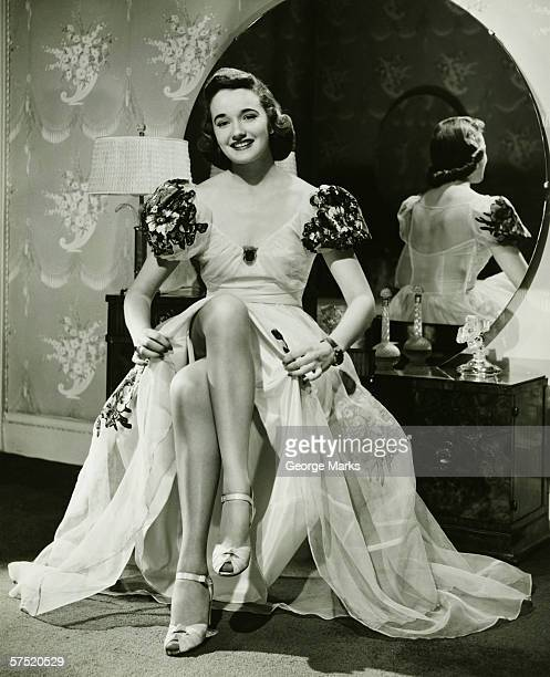 Glamorous woman in evening gown showing legs, portrait, (B&W)