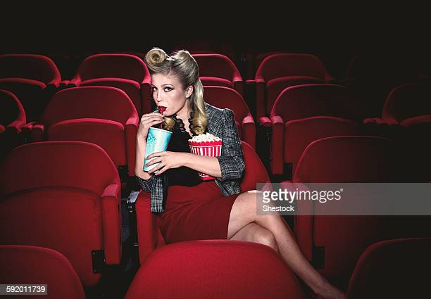 Glamorous woman in vintage clothing watching movie in theater