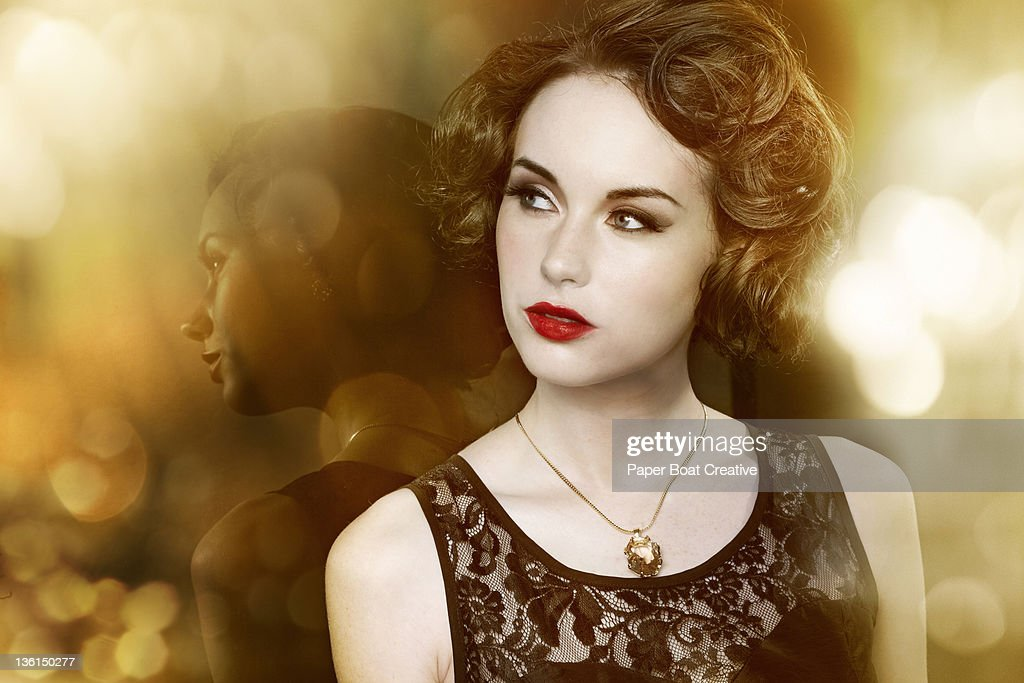 glamorous woman leaning against her own reflection