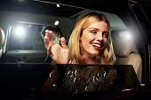 Glamorous woman waving through the window of a limousine