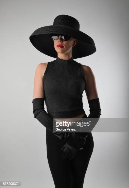 Glamorous woman wearing vintage fashion including black hat with evening gloves
