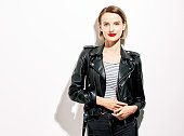Glamorous young woman in black leather jacket on white background with mobile phone