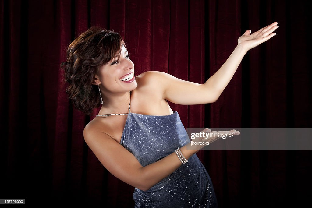 Glamorous Young Woman Presenting at Red Curtain