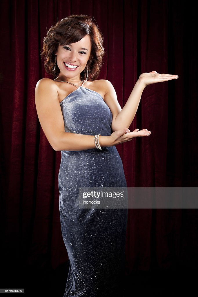 Glamorous Young Woman Presenting in Front of Red Curtain