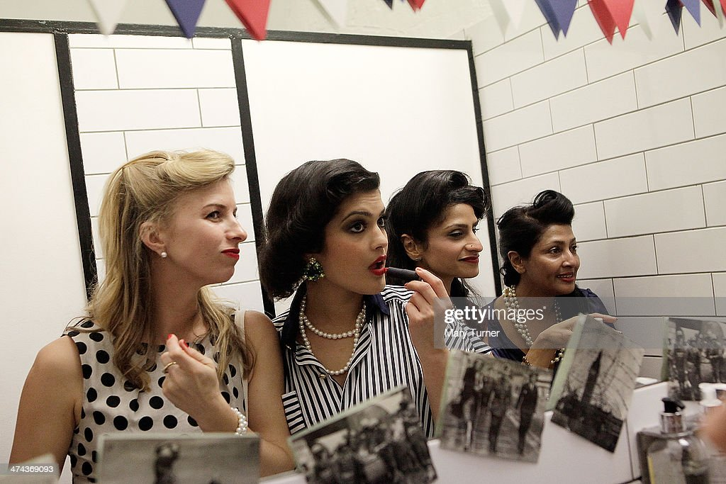 Glamorous young women with classic Victory Rolls in their hair and wearing wartime dress touch up their lipstick, during The Blitz Party on February 22, 2014 in London, England. Deep in an East End bunker hundreds of vintage enthusiasts partied like it was 1940 in a range of vintage costumes. The retro enthusiasts danced to Swing and Jazz music from the era while drinking themed cocktails ordered at the Spitfire Bar, as they embraced the glamour of the era.