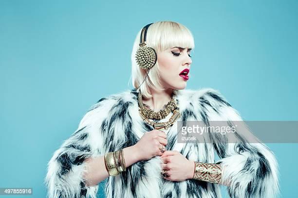 Glamour femme blonde portant veste en fourrure et or bijoux