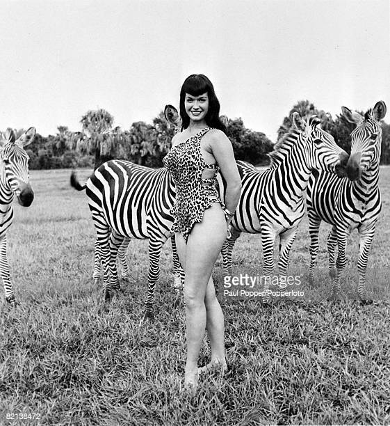 1954 American pinup glamour model Bettie Page born Nashville Tennessee pictured here in a statuesque pose alongside zebras while on a modelling...