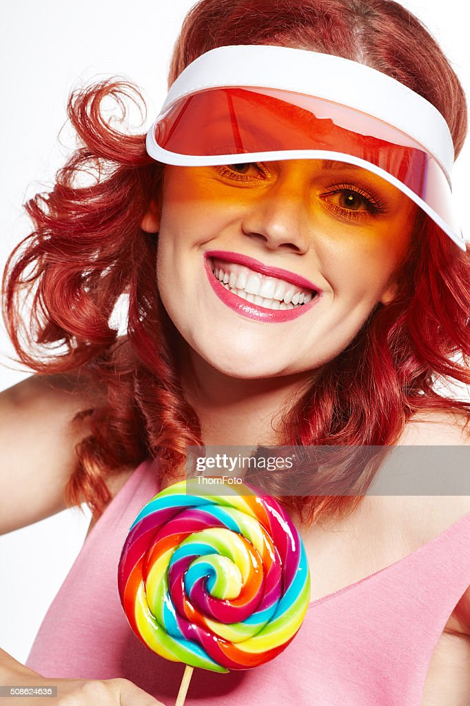 Glamourous girl wearing hat holding lollipop : Stock Photo