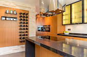 Glamourous kitchen with wooden cabinets and wine racks