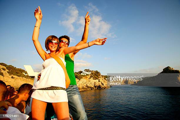 A glamourous trendy couple dancing on a boat party Ibiza 2005