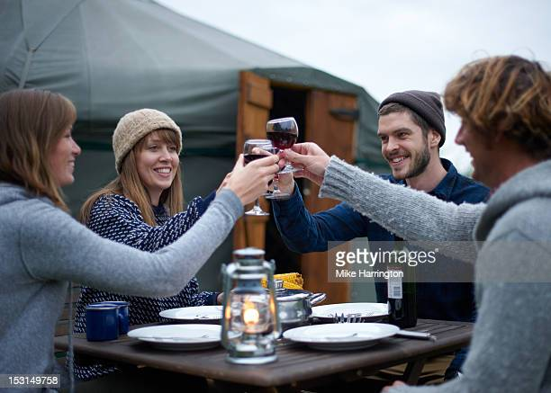 Glampers sharing a toast over bottle of red wine.