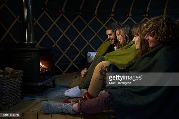 Glampers sitting around fire inside yurt,