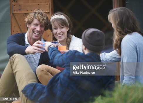 Glamping couples outside yurt sharing a toast. : Stock Photo