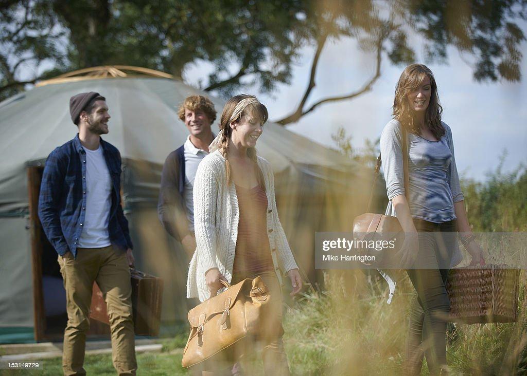 Glamping young people walking outside yurt. : Stock Photo