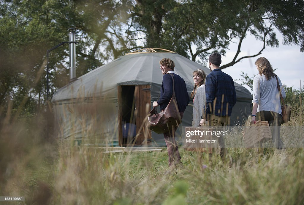 Glamping young people walking towards yurt. : Stock Photo