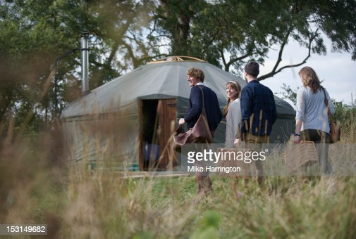 Glamping young people walking towards yurt. : Stock Photo