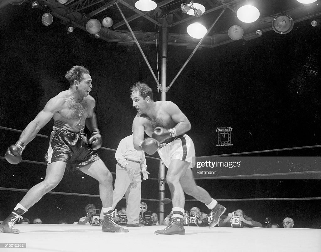 <a gi-track='captionPersonalityLinkClicked' href=/galleries/search?phrase=Rocky+Marciano&family=editorial&specificpeople=94011 ng-click='$event.stopPropagation()'>Rocky Marciano</a> (right) and <a gi-track='captionPersonalityLinkClicked' href=/galleries/search?phrase=Archie+Moore&family=editorial&specificpeople=93092 ng-click='$event.stopPropagation()'>Archie Moore</a> glare at each other in the wild sixth round just before Rocky floored the challenger for the first of two knockdowns. Rocky retained his crown at the Yankee Stadium tonight when he kayoed Moore in the ninth round.