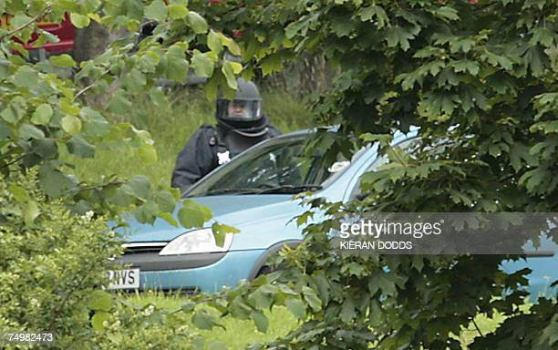 A bomb disposal expert examines a vehicle at Paisley's Royal Alexandra Hospital in Glasgow Scotland 02 July 2007 Police arrested two more people...