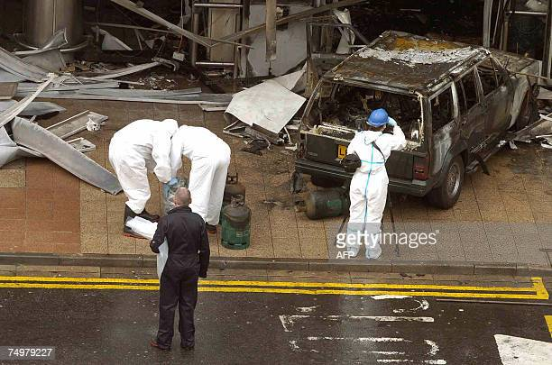 British forensics police officers remove gas cannisters from the burnt wreckage of a vehicle use to ram a passenger terminal at Glasgow Airport in...