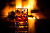 Glass of alcoholic drink wine in front of warm fireplace. Magical relaxed cozy atmosphere near fire