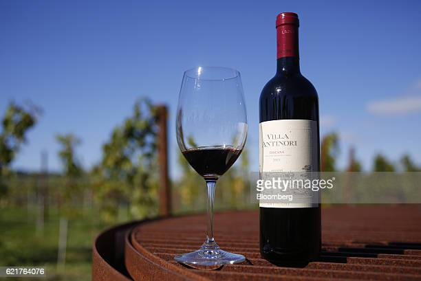 A glass and bottle of Villa Antinori Toscana 2013 red wine produced by Marchesi Antinori SpA sit on display in this arranged photograph at the...