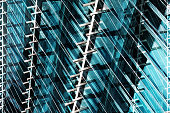 Double exposure photo of modern office building fragment. Glass and metal. Abstract contemporary architecture in shades of blue color.