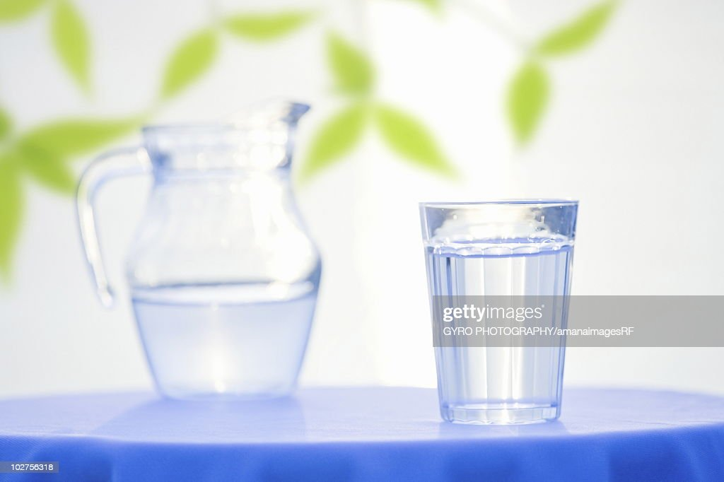 Glass and pitcher with water on table, white background : Stock Photo