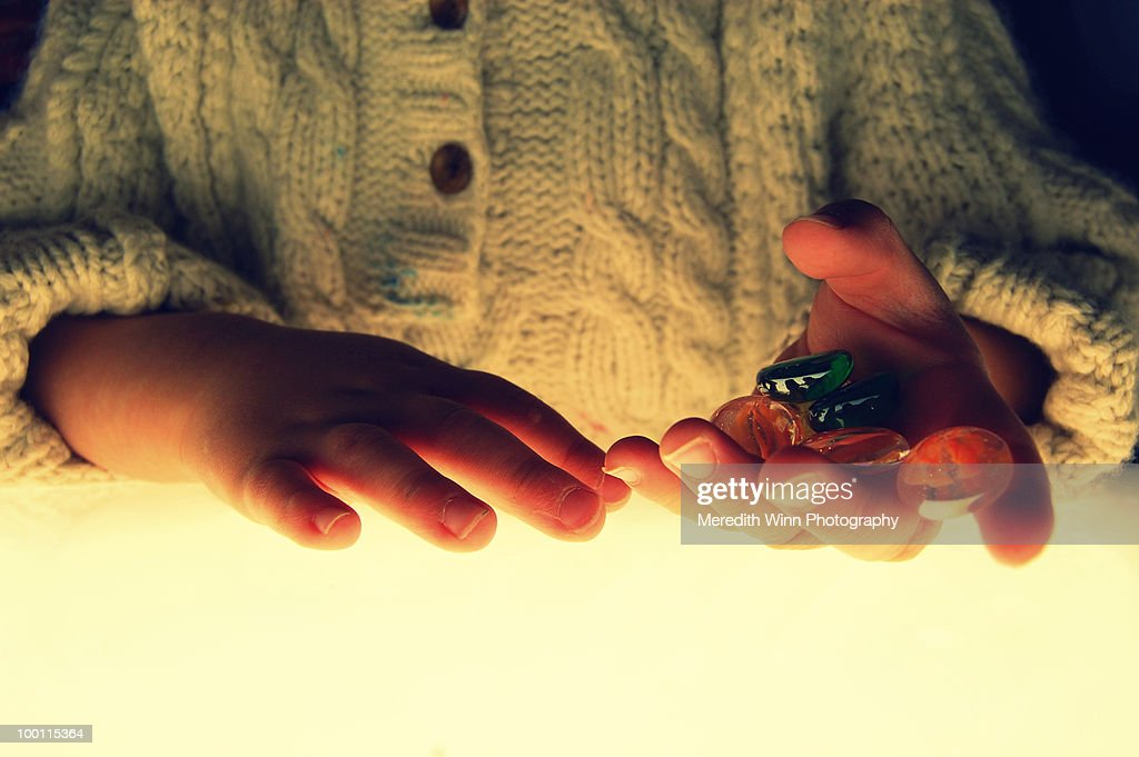 Glass beads in a child's hand : Stock-Foto