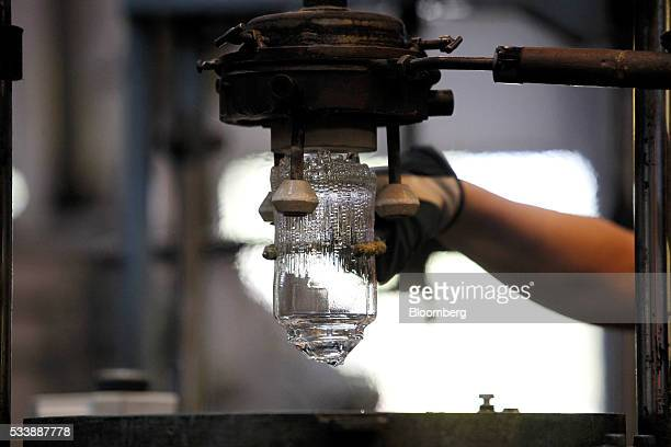 A glass blower prepares to cut an Ultima thule style glass in the workshop during manufacture using traditional methods at the Iittala Oyj glass...