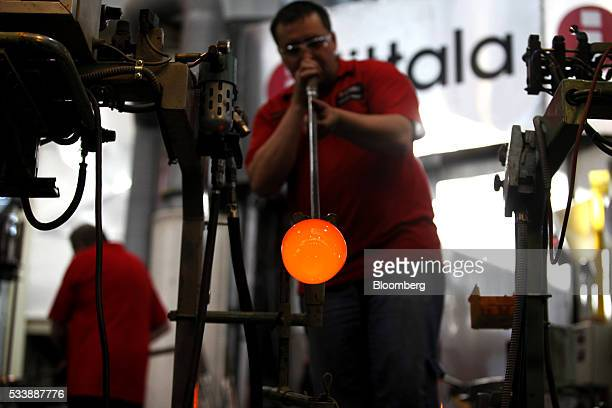 A glass blower uses traditional methods to shape an Aalto style vase in the workshop at the Iittala Oyj glass factory operated by Fiskars Oyj in...