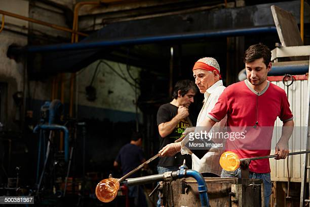Glass blowers working on molten glass
