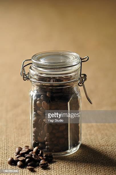 A glass bottle and coffee bean