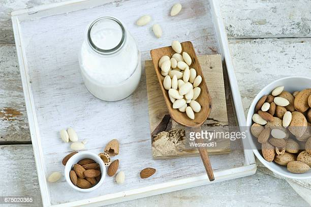 Glass bottle of homemade almond milk, whole and cracked almonds