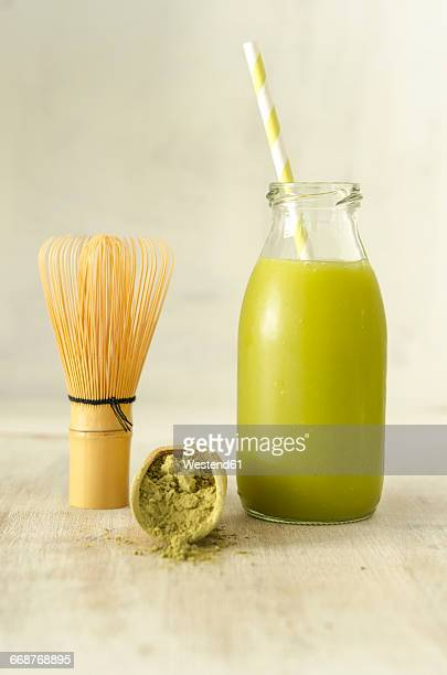 Glass bottle of Matcha smoothie, matcha powder and tea whisk