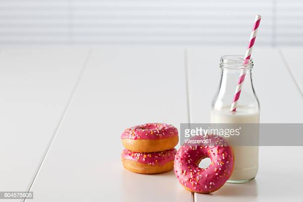 Glass bottle of milk and three doughnuts with pink icing on white ground