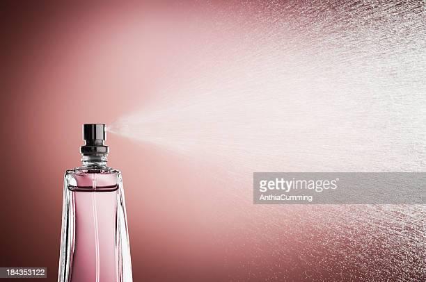 Vetro bottiglia di profumo Spruzzare profumo contro Sfondo rosa