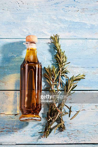 Glass bottle of rosemary oil and twig of rosemary on light blue wood