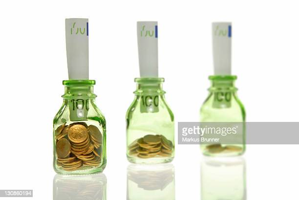 Glass bottles filled with coins and 100-Euro bills