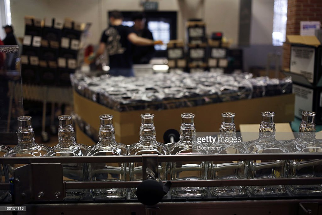 Glass bottles move down a conveyor belt on the Jack Daniel's Single Barrel Select Tennessee Whiskey bottling line at Jack Daniel's Distillery in Lynchburg, Tennessee, U.S., on Thursday, Jan. 30, 2014. Jack Daniel's is owned by Brown-Forman Corp., which announced a regular quarterly cash dividend of 29 cents per share on its Class A and Class B Common stock last week in a company press release. Photographer: Luke Sharrett/Bloomberg via Getty Images