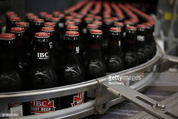 Glass bottles of IBC Root Beer move down a conveyor belt after being filled at the Dr Pepper Snapple Group Inc bottling plant in Irving Texas US on...